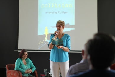 PJ reading an extract from Collision, in background Tima Maria Lacoba author interviewer