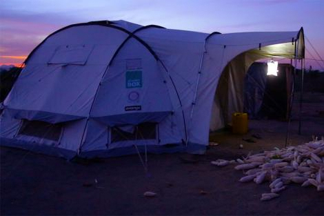 Image of ShelterBox relief tent at dusk with a Luminaid solar light hanging in the porch